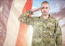 Soldier saluting against a fluttering american flag Stock Photos