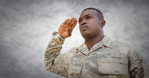 Soldier saluting against white wall with grunge overlay Royalty Free Stock Photography