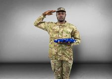 Soldier saluting and with flag in the other hand. concrete room Royalty Free Stock Photo