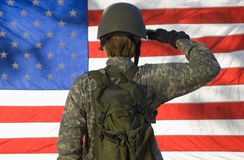 Soldier Saluting In Front Of American Flag. Rear view of a female soldier saluting in front of American flag stock image