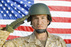 Soldier Saluting In Front Of United States flag. Closeup portrait of a male soldier saluting in front of United States flag stock photo