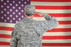 Soldier Saluting Old American Flag. Closeup of a middle aged American soldier in fatigues saluting an old and weathered flag. The flag fills the frame and is out Stock Photography