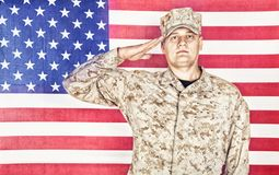 Soldier saluting to national flag of United States stock photos