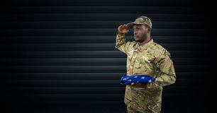 Soldier saluting with the USA flag in his hand. dark background Royalty Free Stock Photo