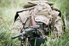 Soldier securing his perimeter - closeup. Special forces soldier hidden in high grass on the battlefield stock photography