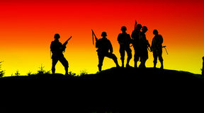 Soldier shiluettes. The shiluette of soldiers with red yellow sky Royalty Free Stock Photos
