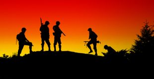 Soldier shiluettes. The shiluette of soldiers with red sky Stock Photo