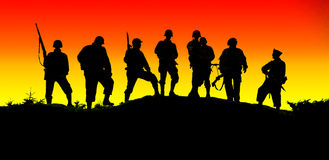Soldier shiluettes. The shiluette of soldiers with a red yellow sky Royalty Free Stock Images