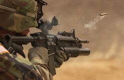Soldier shooting from automatic rifle Royalty Free Stock Image