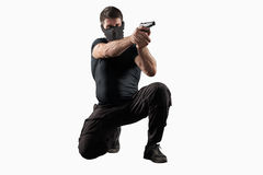 Soldier shooting gun isolated on white. Man in black uniform and headgear with gun in shooting position isolated on white background royalty free stock photo