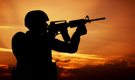 Soldier shooting with his weapon, rifle at sunset. War Stock Photos