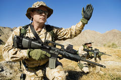 Soldier Signaling During Battle. Soldier with weapon signaling during a battle Stock Images