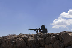 Soldier Silhouette. With blue sky in the background and rock reinforments in the foreground Stock Photo