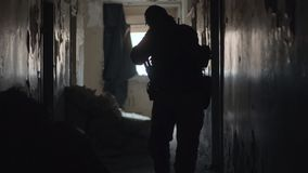 Soldier silhouette with weapon walking in building during military operation. Soldier silhouette with military weapon walking in building. Military man holding stock footage