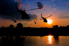 Soldier silhouette in rappelling climb down from helicopter on sunset with copy space add text.  Royalty Free Stock Images