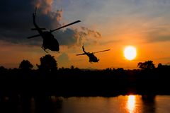 Soldier silhouette in rappelling climb down from helicopter on sunset with copy space add text.  Royalty Free Stock Image