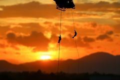 Soldier silhouette in rappelling climb down from helicopter on sunset with copy space add text.  Stock Photos