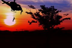 Soldier silhouette in rappelling climb down from helicopter on sunset with copy space add text.  Stock Photography