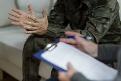 Soldier sitting on the sofa. During psychological therapy Stock Image