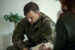 Soldier sitting and talking to his therapist. Concept stock photography