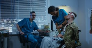 Soldier sitting in wheelchair among doctor and nurse. Medium shot of injured soldier sitting in wheelchair among doctor and nurse stock footage