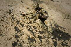 Soldier Sliding Downhill Holding Rifle during Daytime Royalty Free Stock Photo