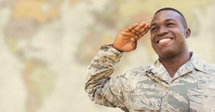 Soldier smiling and saluting against blurry yellowish map Stock Photography