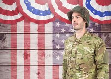 Soldier standing against american flag background Stock Photography