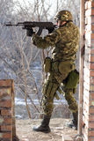 Soldier standing near wall with a gun. In his hands royalty free stock image