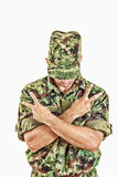 Soldier standing with sign of peace with cross arms. Unknown soldier with hidden face in green camouflage uniform covers face with cap and standing with sign of Royalty Free Stock Image