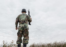 Soldier standing tall with his back turned to camera Royalty Free Stock Photos