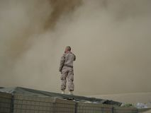Soldier Standing on Top of a Black Tarp Covered Equipments Stock Image