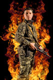Soldier stands with a gun in his hand. And safety glasses in a burning fire Royalty Free Stock Photography