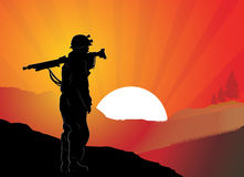 Soldier. Stands at sunset and holding a machine gun Stock Photography