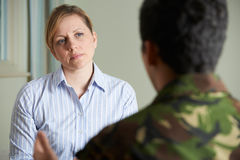 Soldier Suffering With Stress Talking To Counselor stock photo
