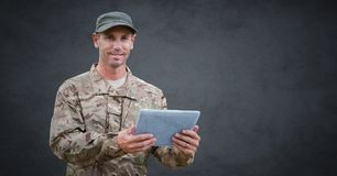 Soldier with tablet against grey background with grunge overlay Royalty Free Stock Image
