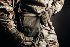 Soldier in tactical gloves using first aid leg bag