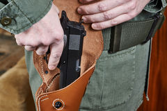 Soldier takes out gun from the holster Royalty Free Stock Photo