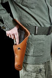 Soldier takes out gun from holster Royalty Free Stock Photography