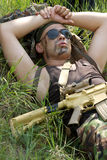 Soldier takes rest lying on a grass Stock Images