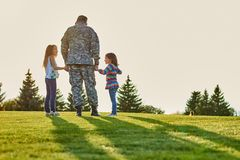 Soldier is talking with daughters, back view. Man in military uniform is holding hands of little daughters, having conversation royalty free stock photo