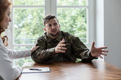 Soldier talking about his war experience with fear. Psychiatrist showing support stock photos