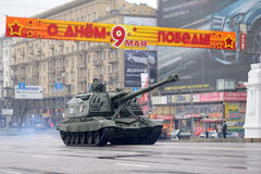 Soldier on tank. Driving by street on the dress rehearsal of the military parade. The congratulation banner is hung Royalty Free Stock Image