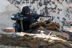 Soldier targeting with an AK-47 automatic rifle. Soldier with a gun in the hideout place Royalty Free Stock Image