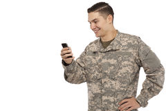 Soldier text messaging. Side view of army soldier text messaging against white background Stock Photos