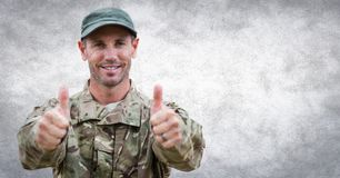 Soldier thumbs up against white wall with grunge overlay Stock Photography