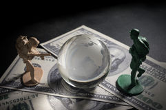 Soldier toys and glass globe on money Stock Photo