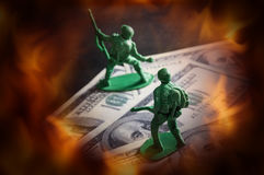 Soldier toys on money with fire screen. Stock Photo