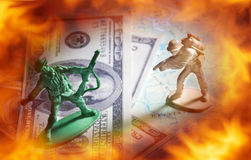 Soldier toys on money and map with fire flame screen. Royalty Free Stock Photography