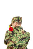 Soldier with turned back holding red rose over shoulder Royalty Free Stock Image